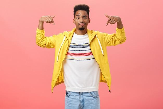 Wat vind je van mijn stijl. coole en knappe stijlvolle jongeman met baard in trendy gele jas over t-shirt die handen opheft die naar zichzelf wijzen, grijnzend en wenkbrauw optrekkend, niet zeker hoe hij eruit ziet.