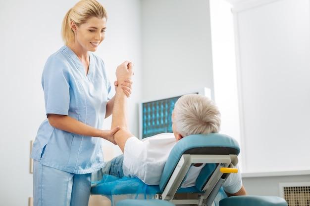 Wat voel je. positieve aardige vrouwelijke arts die de hand van haar patiënten vasthoudt en glimlacht terwijl hij naar hem kijkt