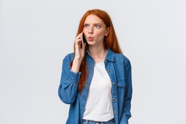 Wat zeg je. intens en gefrustreerd, verwarde roodharige vrouw die gespannen en van streek raakt en slecht nieuws op de telefoon hoort, vriend bellen realiseert zich dat er iets vreselijks is gebeurd, witte muur