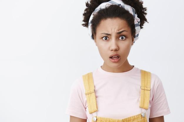 Wat zeg je. portret van verwarde en boos knappe afro-amerikaanse vrouw in hoofdband en schattige gele overall, wenkbrauw optrekkend, staande met geopende mond geen idee en ondervraagd