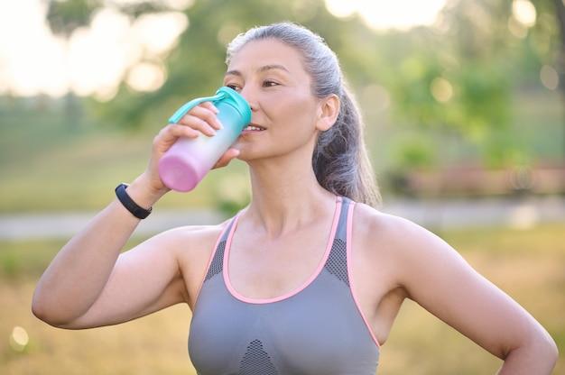 Water balans. een vrouw in sportkleding met een fles in handen