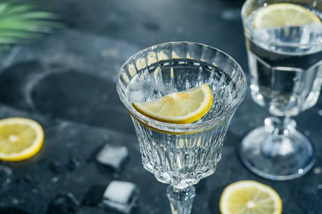 Water citroen detox. zuiver koud water met citroen in kristallen glazen op een donkere achtergrond in de zonnige zomerzon