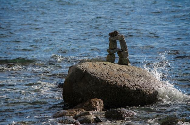 Water dat op een inuksuk in de engelse baai van stanley park, vancouver, bc, canada bespat