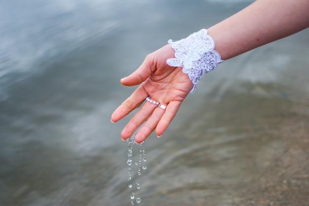 Water dat uit de handen van een bruid in een rivier druipt