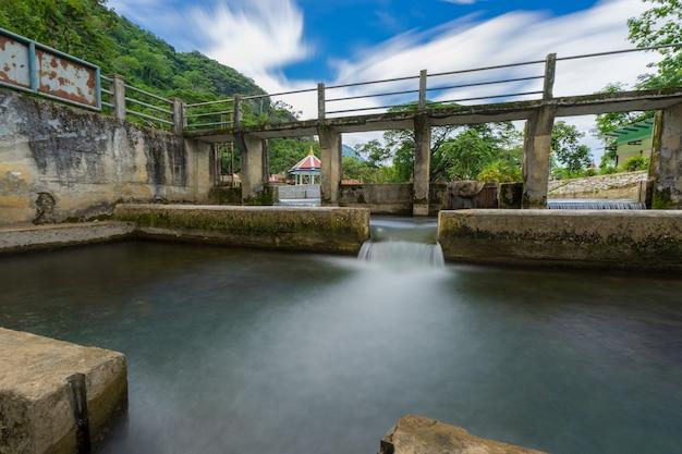 Water die van de dam, stroomgebied in platteland thailand stromen