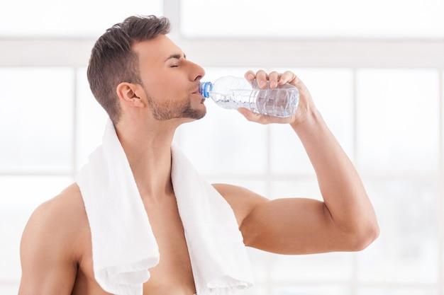 Water drinken na de training. knappe jonge gespierde man met handdoek op schouders drinkwater en ogen gesloten houden