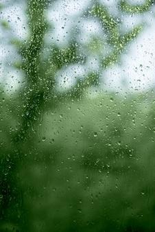 Water druppels op venster over groene abstracte achtergrond. regen concept