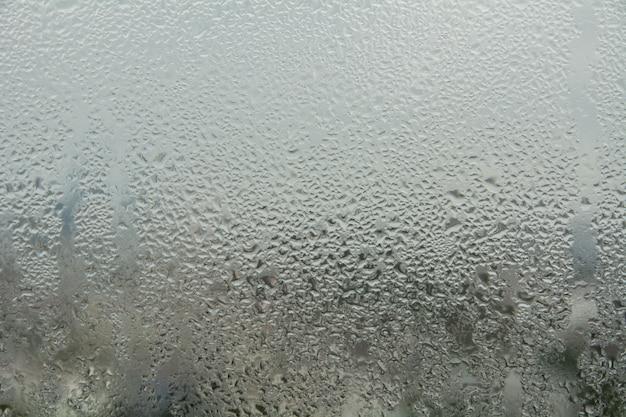 Water druppels van thuis condensatie op een venster