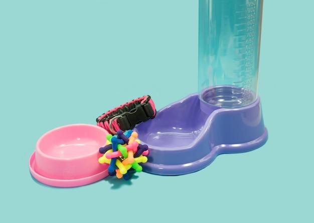 Water feeder met rubber speelgoed en kragen op blauwe achtergrond