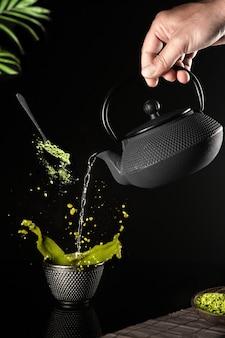 Water gegoten in een donkere kop matcha-thee op een zwarte achtergrond. verticaal formaat.