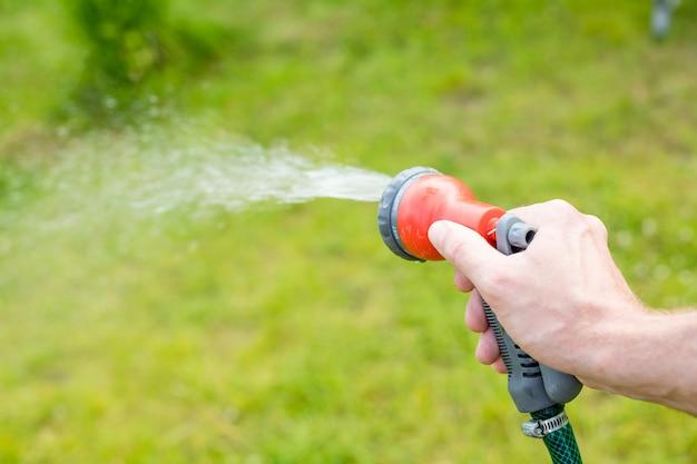 Water geven bedden en planten in de zomertuin van sprinkler.watering gazon gras met een douchekop hoofd. handmatige irrigatie irrigeert bloembedden, een groen gazon en bloeiende struiken. slang