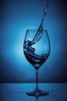 Water gieten in een transparant glas voor wijn. blauwe achtergrond met waterspatten