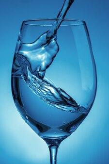 Water gieten in een transparant glas voor wijn close-up. lichtblauwe achtergrond met waterspatten