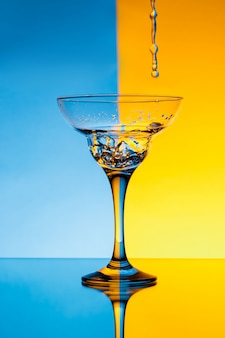 Water gieten in glas over blauwe en gele muur