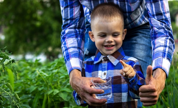 Water in een glas in de handen van een kind en vader. natuur.