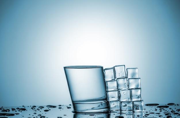 Water in glas en ijsblokjes, liggend naast