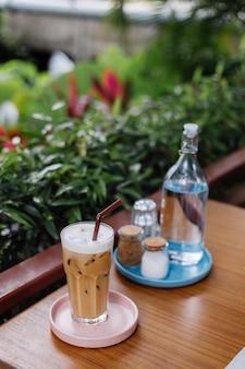 Water in glazen fles iced latte op een roze stand zout en papier op houten tafel