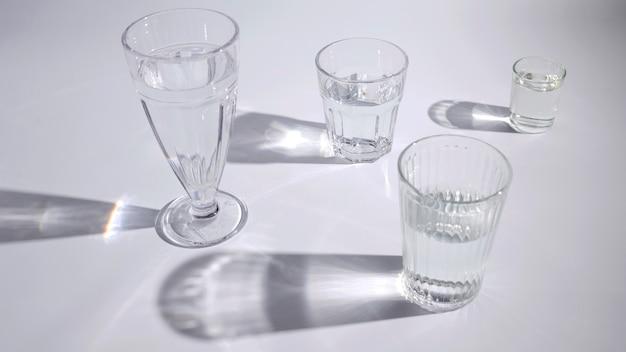 Water in het verschillende type glazen met schaduw op witte achtergrond