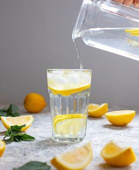 Water met citroen, munt en ijs. water wordt uit een glazen kan in een glas gegoten. detailopname.