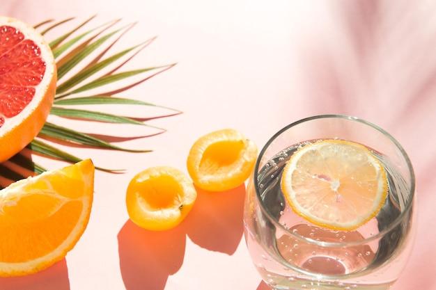 Water met ijs en citroen koele zomerdranken gezond voedsel fruit en frisdrankglas op roze kleur backg