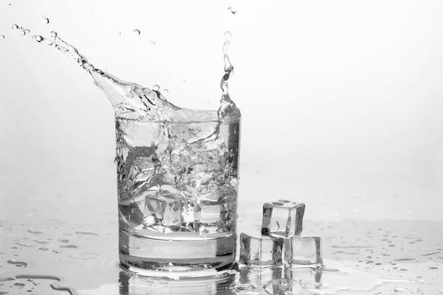 Water met ijs in een glas met spatten
