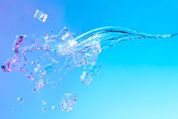 Water met ijsblokjes in levendige, opvallende paarse en blauwe holografische kleurverlooplichten. concept kunst. minimaal zomersurrealisme.