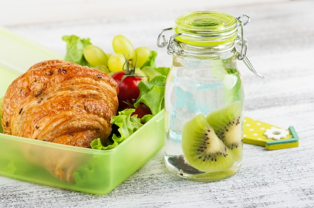 Water met kiwi en groene lunchbox