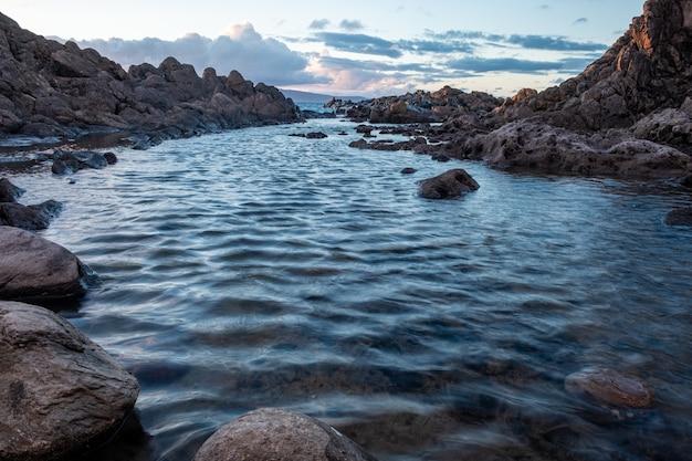 Water met stenen erin, bedolven onder rotsen