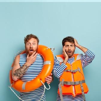 Water redden concept. beschaamde mannelijke strandwachten staren verbaasd naar de camera, dragen een matroos-trui, oranje veiligheidsvest