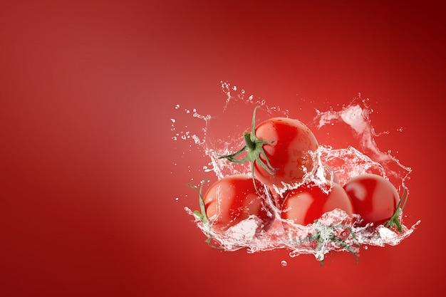 Water spatten op verse rode tomaten over rood