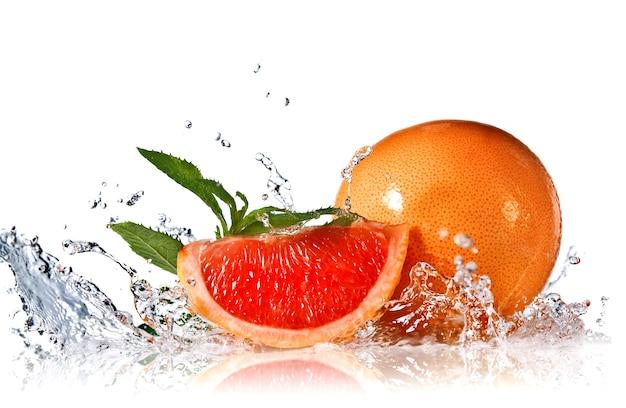Water splash op grapefruit met munt geïsoleerd op wit