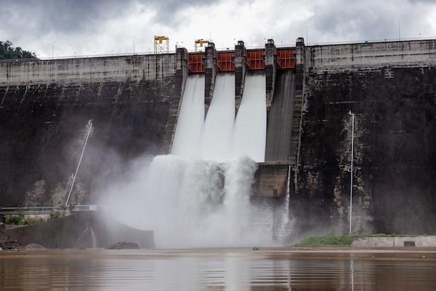 Water stroomt over sluizen van een dam in khun dan prakan chon