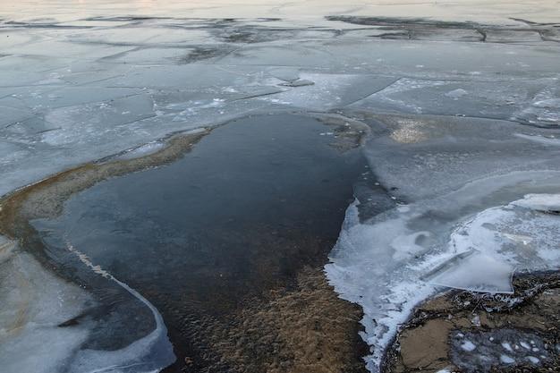 Water stroomt tussen ijsschotsen. het oppervlak van een bevroren rivier op een winterse dag.