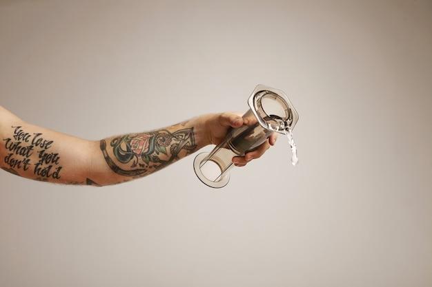Water stroomt uit een lichtgrijze heldere aeropress vastgehouden door een getatoeëerde jongeman, van dichtbij