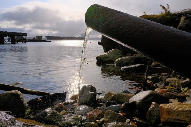 Water stroomt uit een roestige pijp naar het kustgedeelte de barentszzee