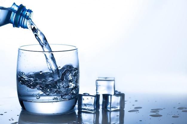 Water uit de fles gieten in de buurt van ijsblokjes