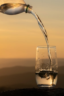 Water uit een fles gieten in een schoon glas transparant drinkwater mineraalwater tegen de rug...