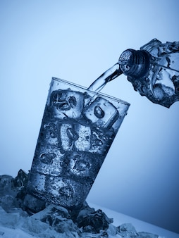 Water uit een plastic fles gieten in een glas met ijs op een lichtblauwe achtergrond