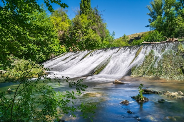 Water waterval glijdend van stenen muur in groene plant bos. duraton, sepulveda, segovia,