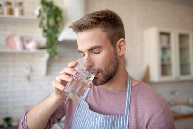 Waterbalans behouden. een jonge, bebaarde man die schoon water drinkt