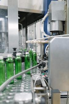 Waterbottellijn voor het verwerken en bottelen van zuiver mineraalwater in kleine groene glazen flessen. selectieve aandacht.