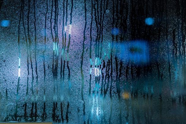 Waterdaling op venster, onduidelijk beeldaardachtergrond met condensatie