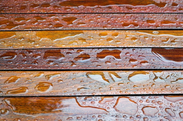 Waterdalingen op een houten vloeroppervlakte druppel water op hout met regendruppel na een regen.