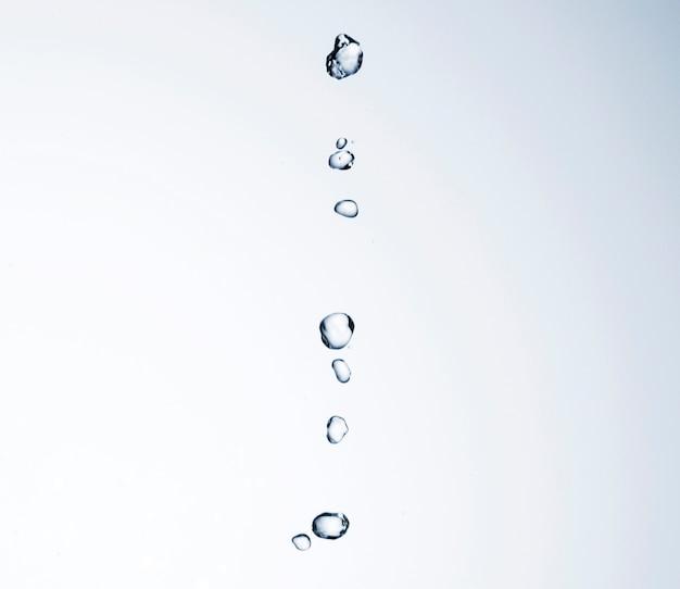 Waterdalingen op wit close-up als achtergrond