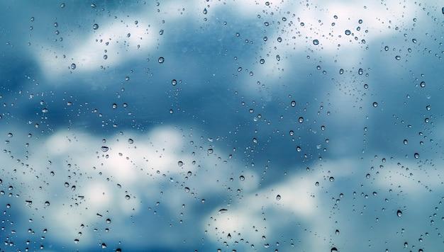 Waterdruppels op glas, op hemelachtergrond, achtergrond of textuur