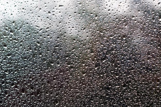 Waterdruppels op glas tegen de hemel en bomen.
