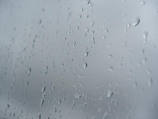 Waterdruppels op glas tegen een grijze bewolkte hemel