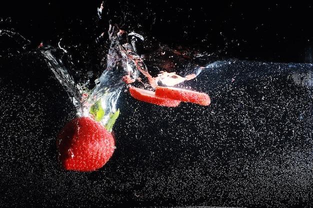 Waterdruppels op rijpe zoete aardbei. verse bessenachtergrond met exemplaarruimte voor uw tekst. veganistisch voedselconcept.