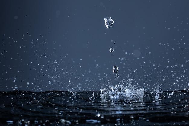 Waterdruppels vallen op een zwart oppervlak