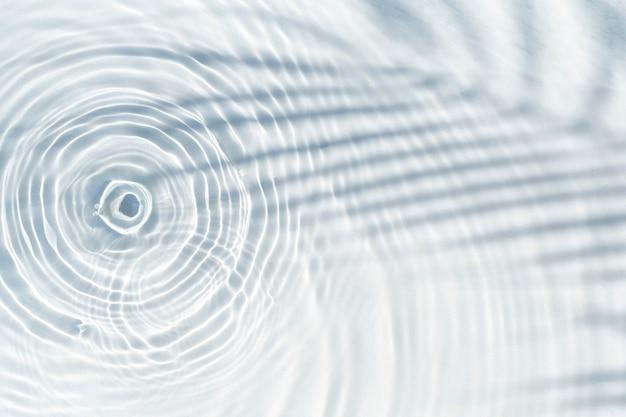 Waterdruppels vallen op het transparante oppervlak van het water en de schaduw van een palmblad. bovenaanzicht, plat gelegd.